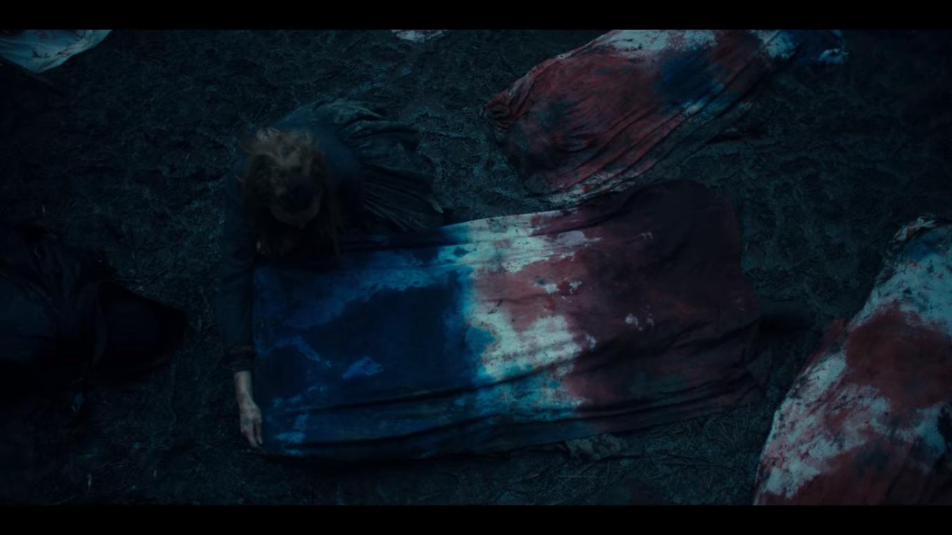 Cena da série La Révolution, Netflix, 2020. A personagem líder dos revolucionários, cobre os mortos com um pano manchado pelo sangue azul dos nobres e o sangue vermelho do povo.