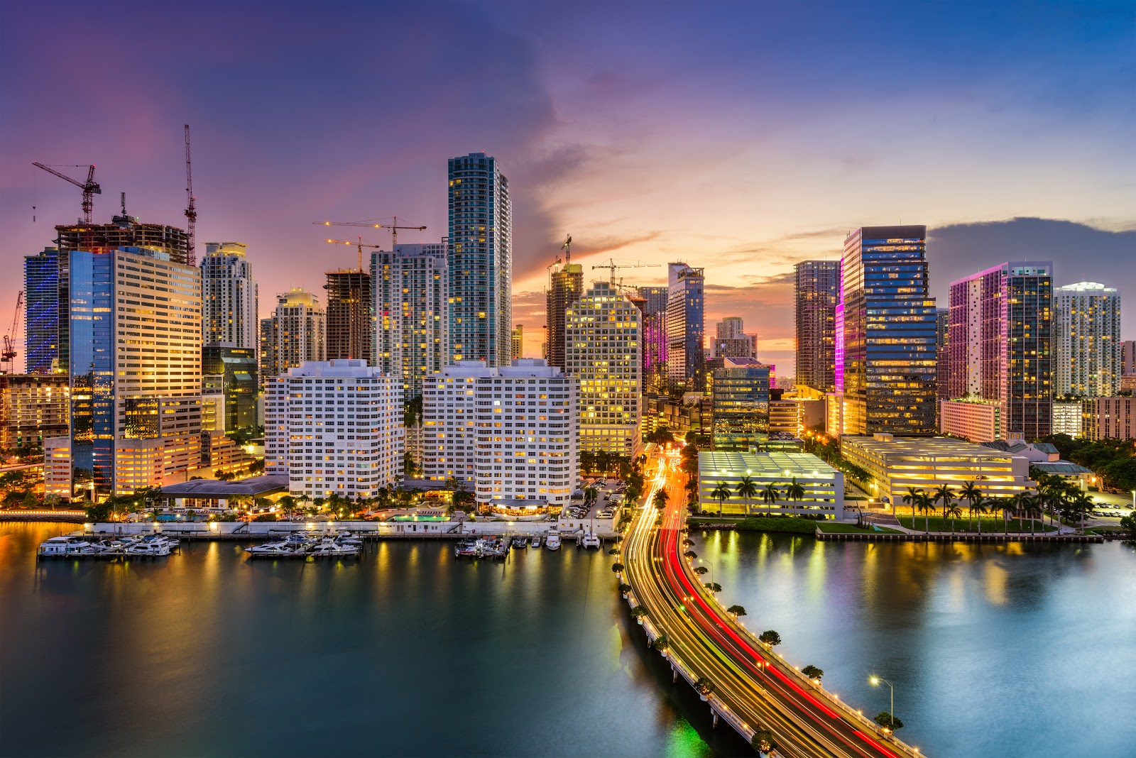 Skyline of Miami at night. It displays many high rise buildings and traffic.