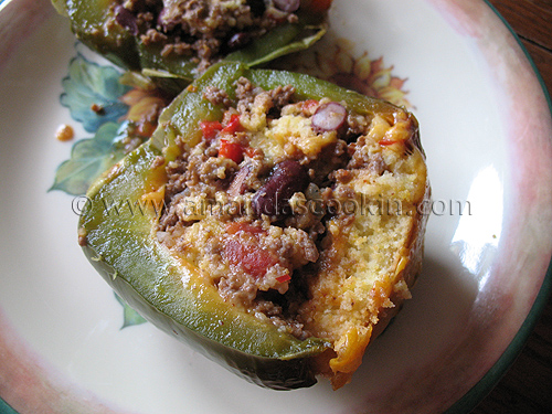 A close up photo of a slice of chili and cornbread stuffed pepper.