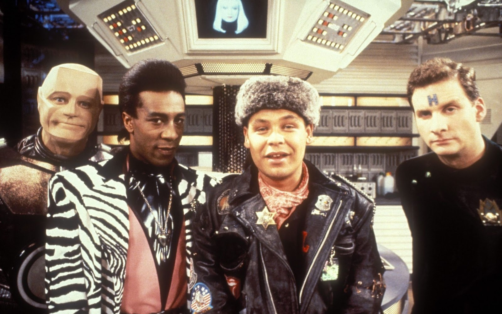 The main characters of Red Dwarf: Kryten, The Cat, Lister and Rimmer.