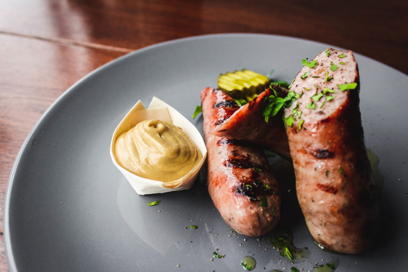 A dish with two halves of homemade skinless sausage.