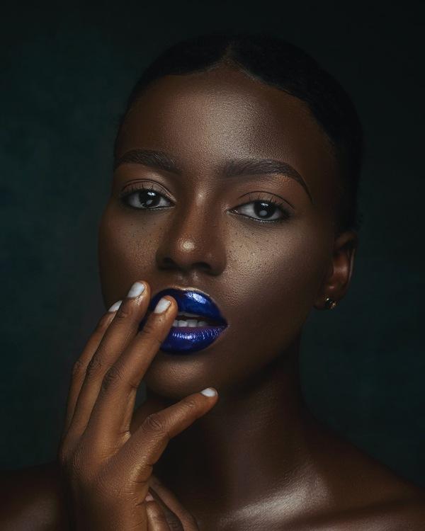 foto de uma mulher negra bem maquiada posando com a mão na boca