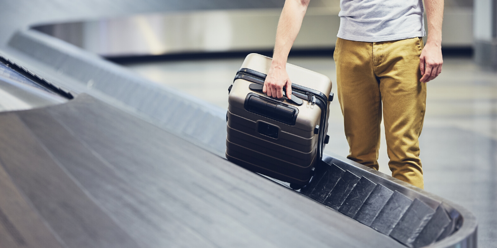 man grabbing bag from conveyor belt at airport