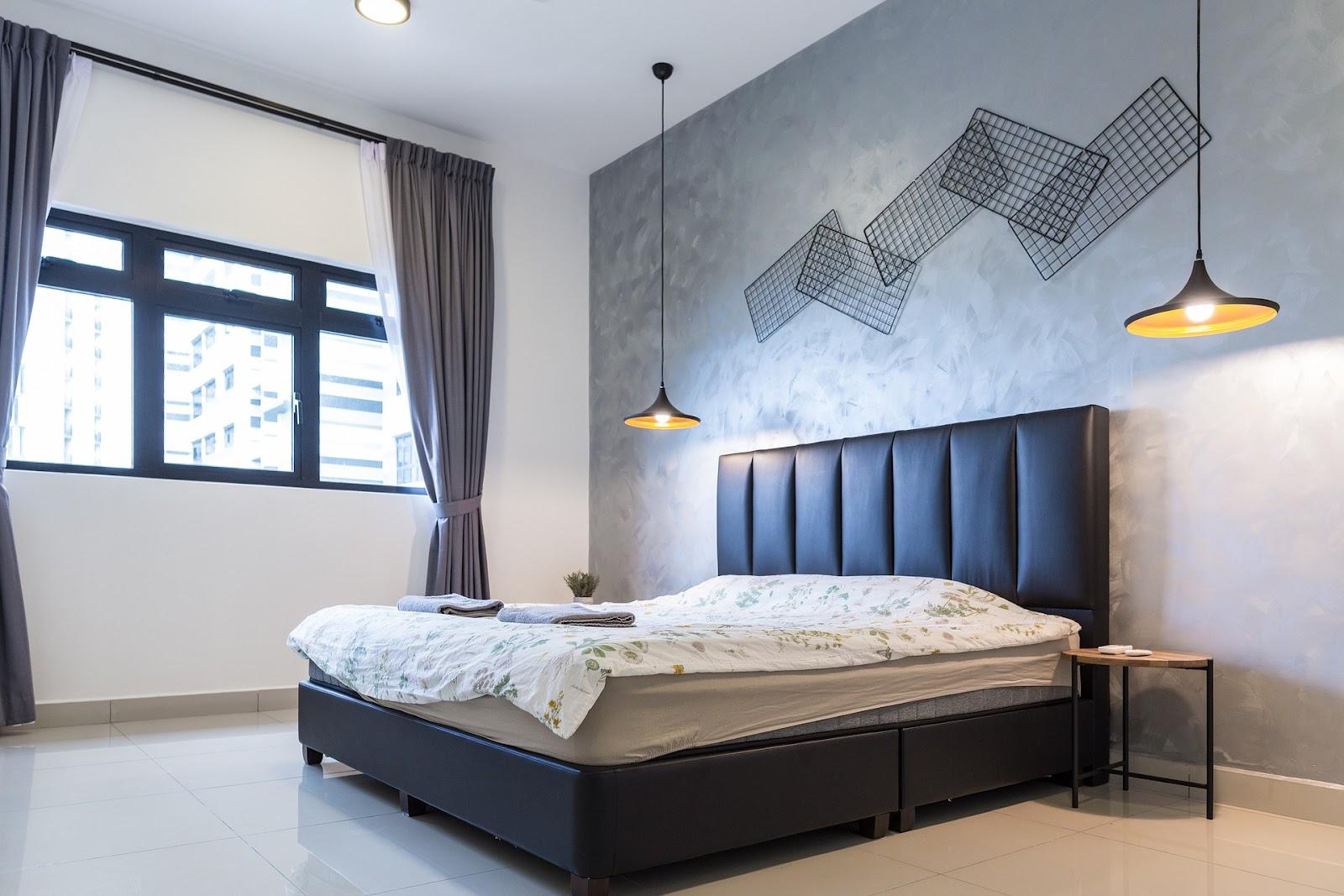 Um quarto com vários memory boards, uma cama com estofado e um pendente.