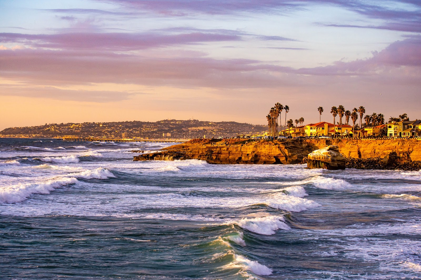 blue ocean waves coming to san diego shore with short cliff and bright buildings and palm trees during sunset in california
