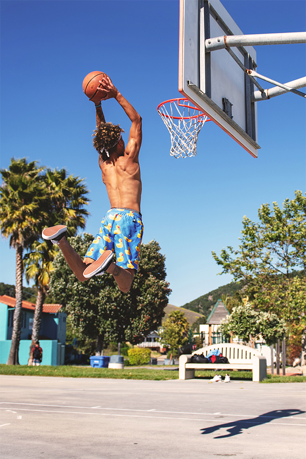 Man leaping mid-air to dunk a basketball on a bright, sunny day.