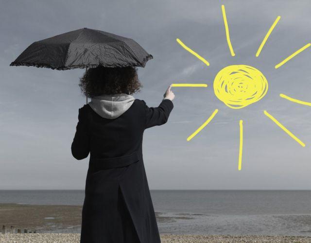 Menina pintando um sol em um céu cinza