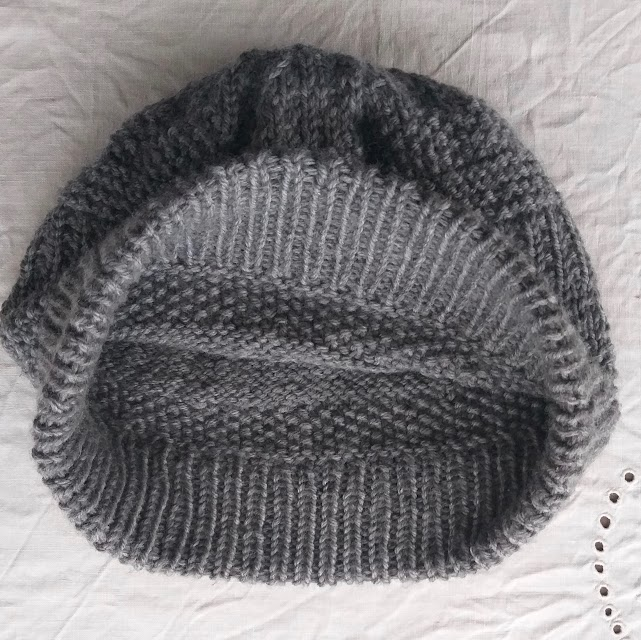 A grey handknit hat with textured stitch pattern and long folded brim, with brim turned out to show the neat inside finish.