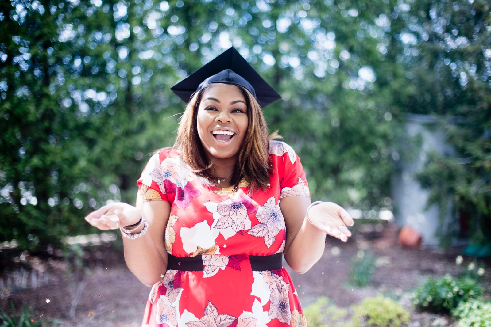 A female graduate smiles while wearing her graduation cap.  STEM scholarships for girls help graduates succeed.