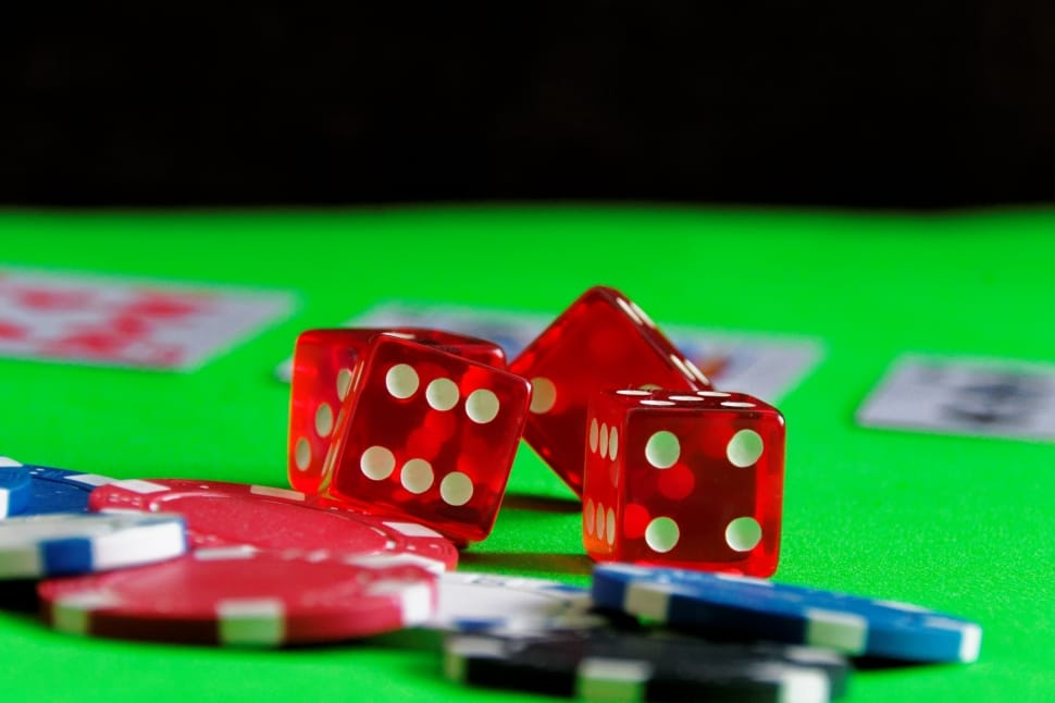 Four red dice and five multicoloured gambling chips rest on a green betting table