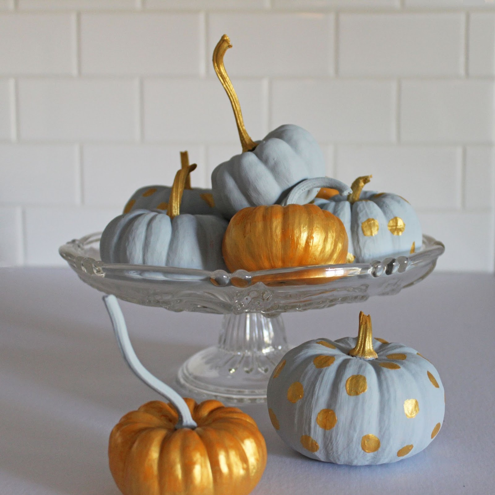 how to use pumpkins in your home to decorate. Images shows Grey and gold pumpkins displayed on a glass cake dish.
