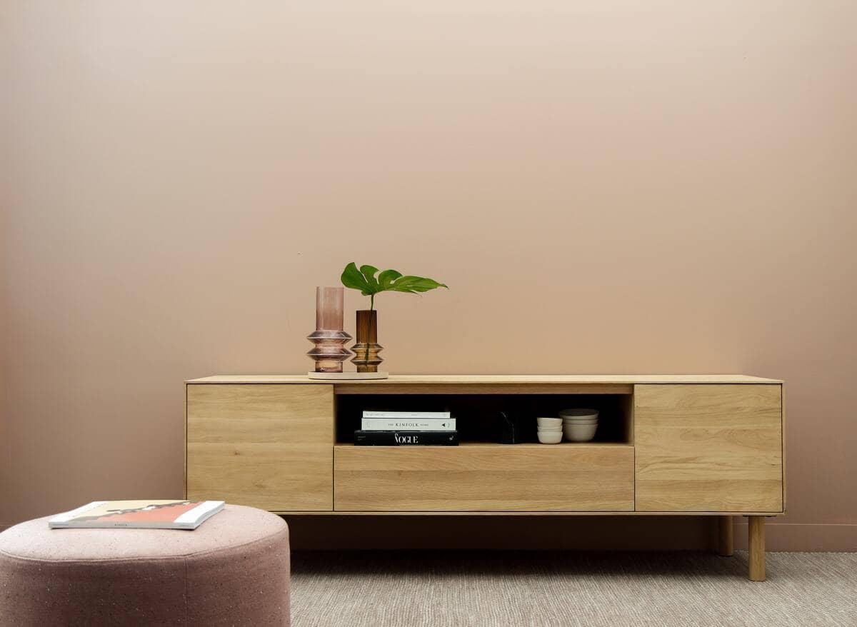 Un mobile per tv in legno con alcune decorazione e un pouf in velluto rosa