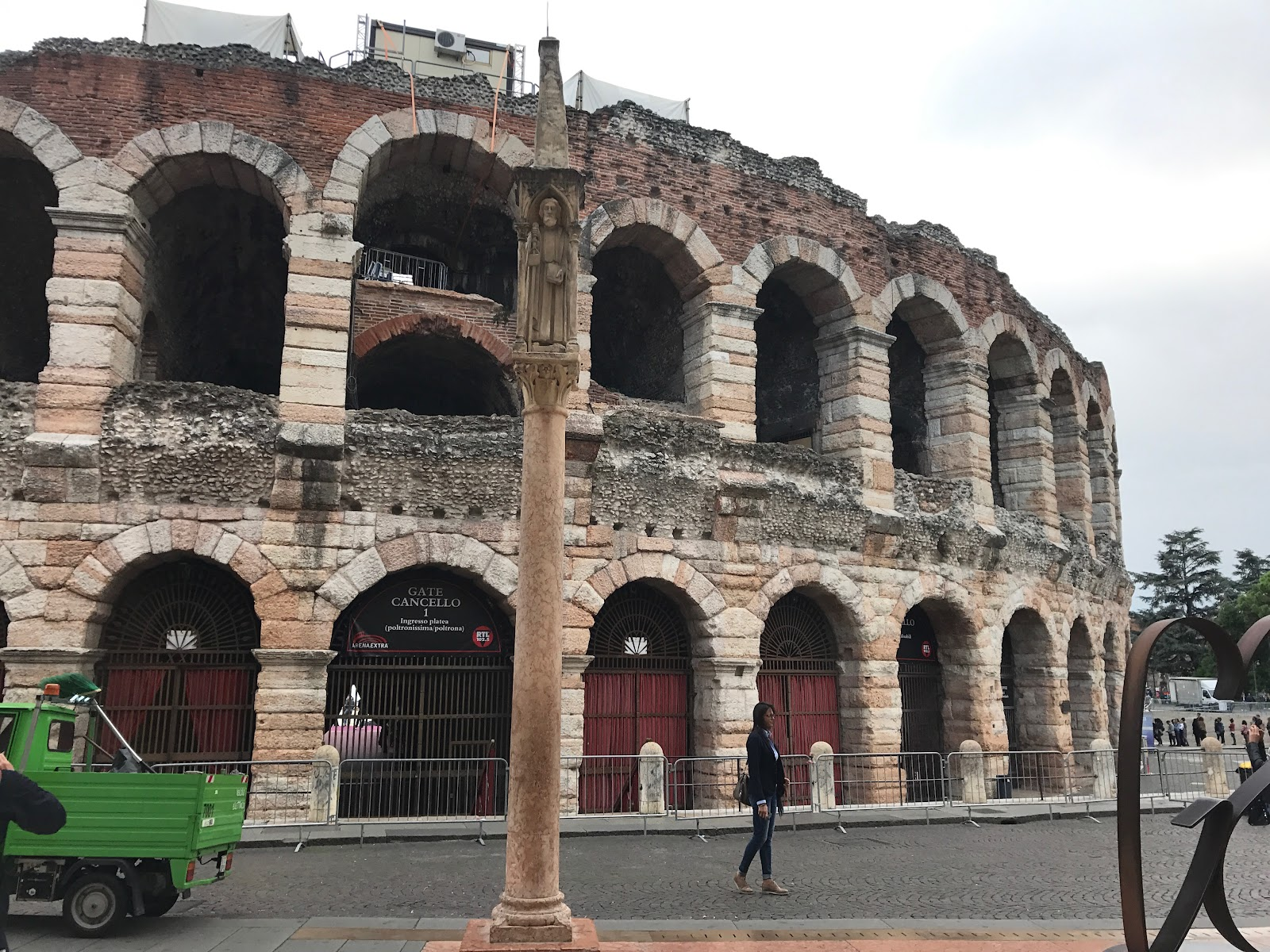 arena di verona, large colosseum is the main attraction in verona, italy. Seen on a cloudy day, tourists in the distance and old column in front of the arena. Be sure to see it on an Italy road trip