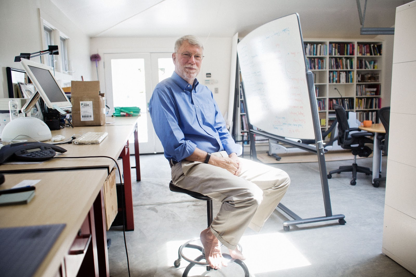 John Seely Brown, co-founder of Calm Design Principles, sits barefoot on a stool in his office.