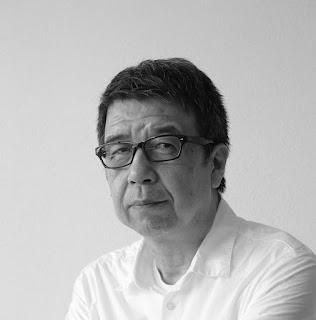 白黒の写真で白いYシャツ着用し、黒縁のメガネをかけた大平義道氏