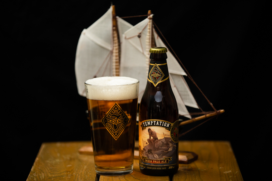 Legend 7 Brewing's 'Temptation' in a bottle and poured into a glass in front of a miniature pirate ship