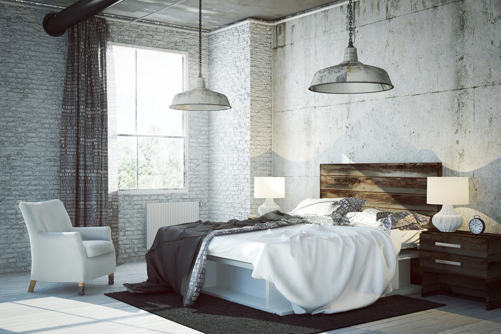 Um quarto industrial com paredes tijoladas, pendentes e cores destacadas chumbo.