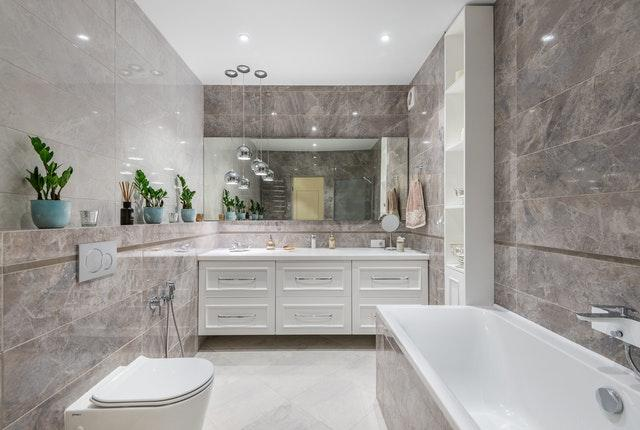 Having large bright bathrooms is great idea, but you can use mirrors elswhere.