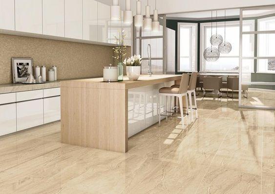 cozinha com armários brancos com piso imitando mármore marrom, bancada de madeira com bancos amadeirados, luminárias pendentes brancas e portas de vidros dividindo o ambiente