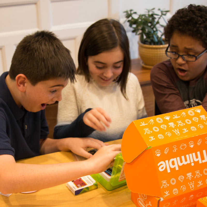 Three students open a Thimble project box and examine the electronic components while smiling and looking surprised.