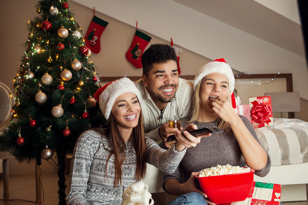 a group of people in room decorated for the holidays watching a movie and eating popcorn