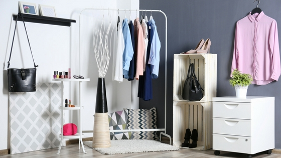 A bedroom with a clothes rack and shelves for organzing
