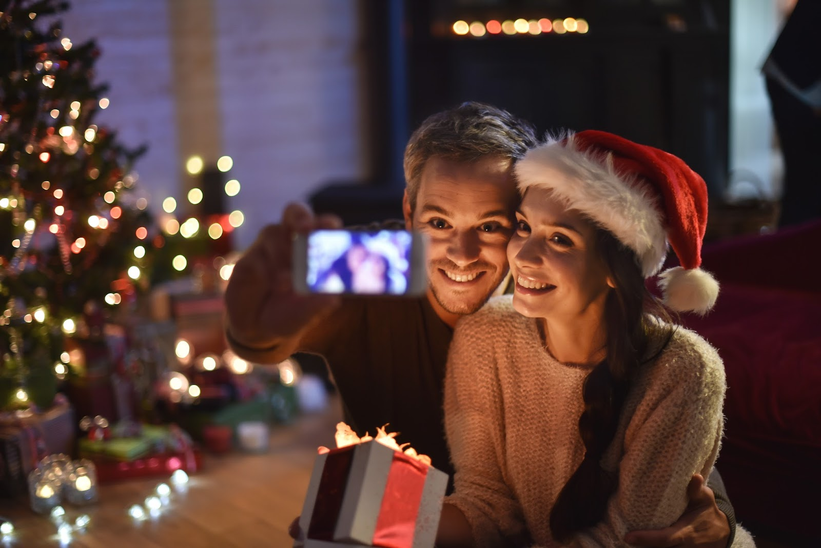 couple taking a selfie with a smartphone the night christmas