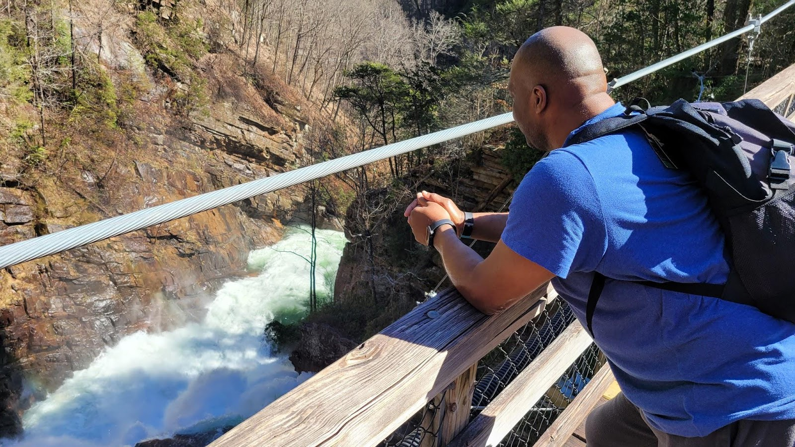 Man looks out into a waterfall while standing on a bridge