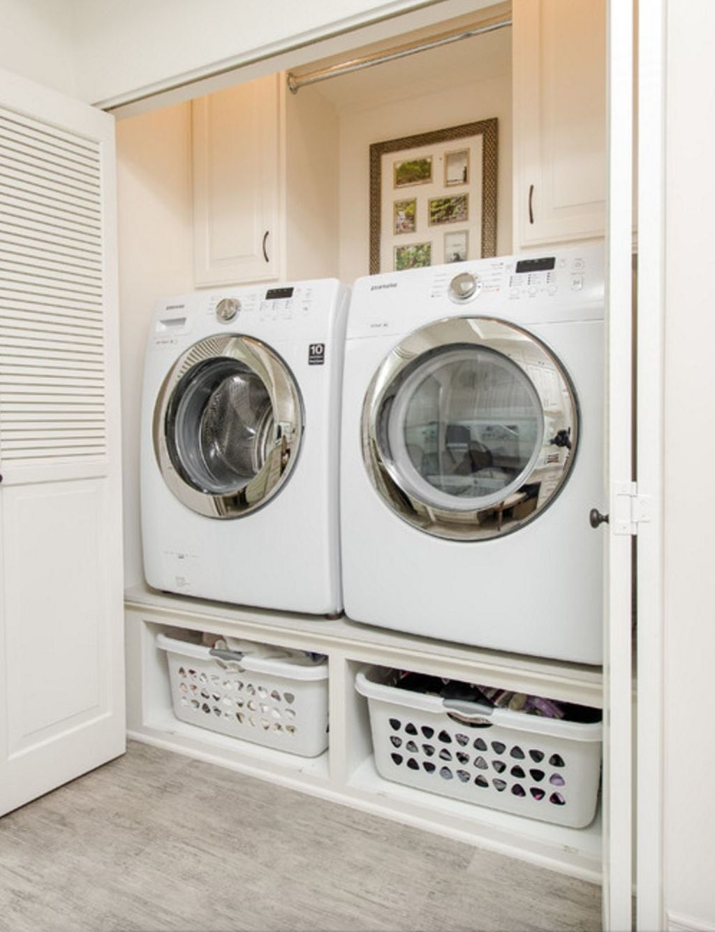 white washer and dryer are stored in closet with custom cabinets and shelving for two laundry baskets