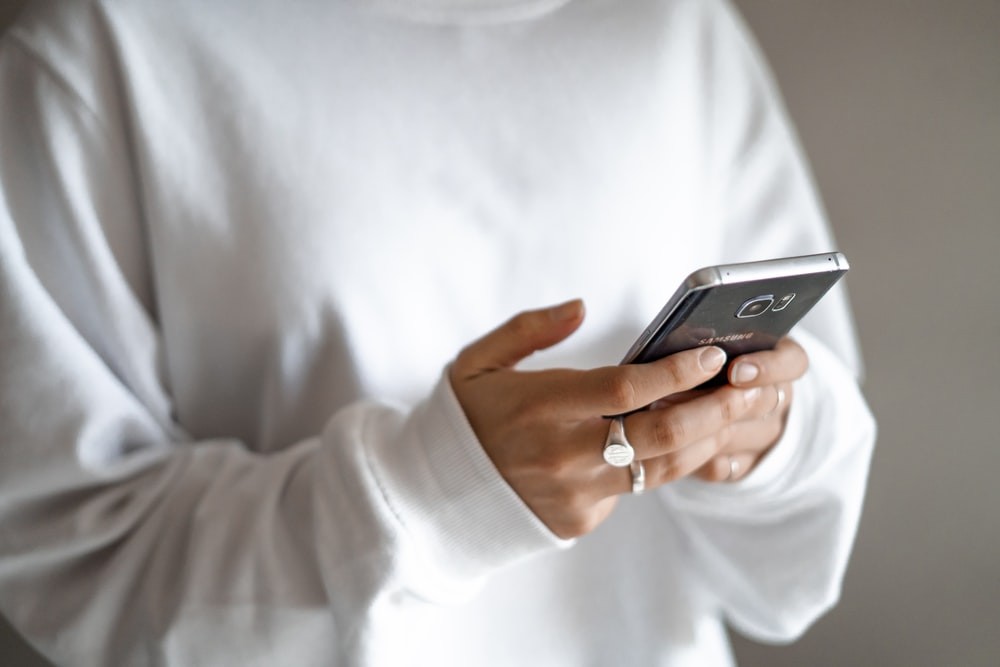 person in white long sleeve shirt holding black smartphone