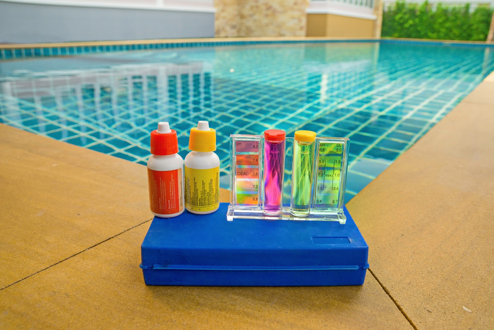 a pool water test kit with colored solutions and test tubes sitting on a blue box next to an inground pool