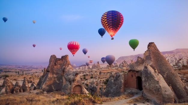 Beautiful hot air balloons flying over cappadocia landscape at sunrise Premium Photo