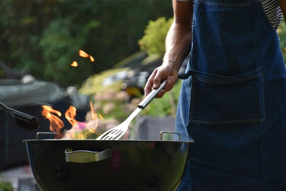 A man cooking on a barbecue.