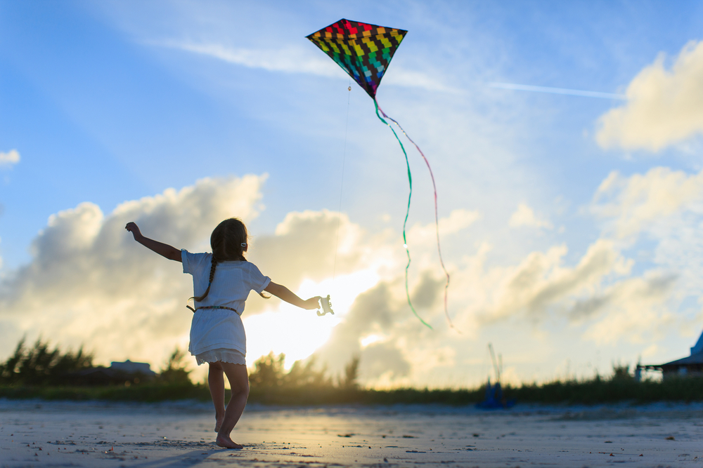 A girl flying a kite on a windy, cloudy day.