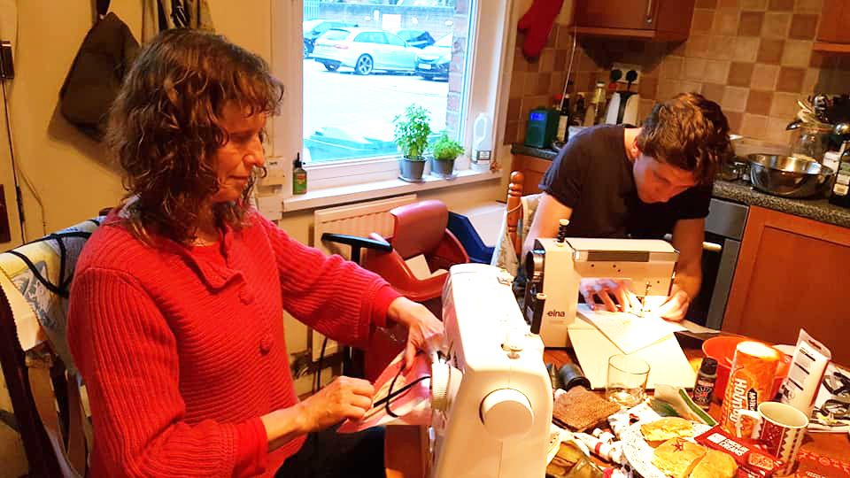 A man and a woman using sewing machines.