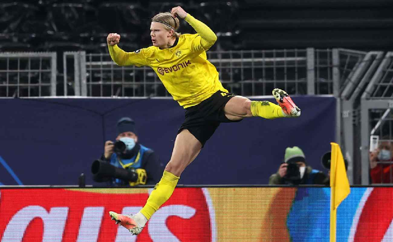 Alt: Erling Haaland jumps in celebration of scoring a goal for Borussia Dortmund - Photo by Lars Baron/Getty Images