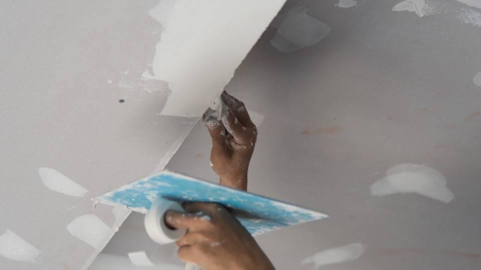 Uma mão fazendo a raspagem do teto.