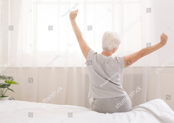 Older woman stretching while sitting on her bed.
