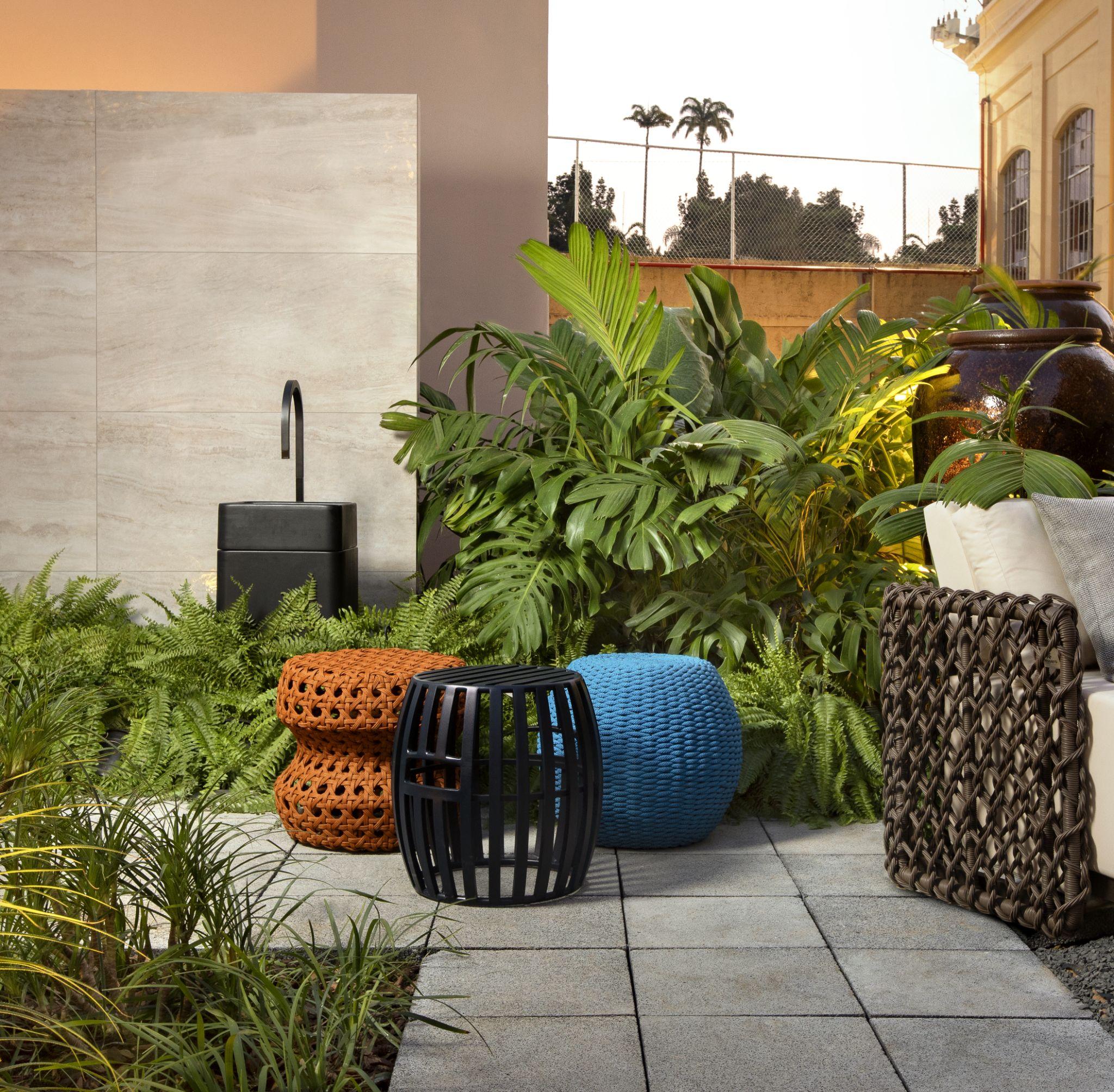 jardim com piso drenante, puffs de crochê, palha e madeira, plantas e luz de led iluminando