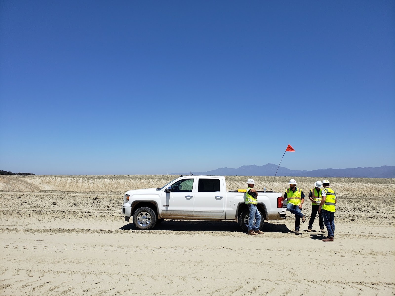 Construction industry workers out on site with white pickup truck