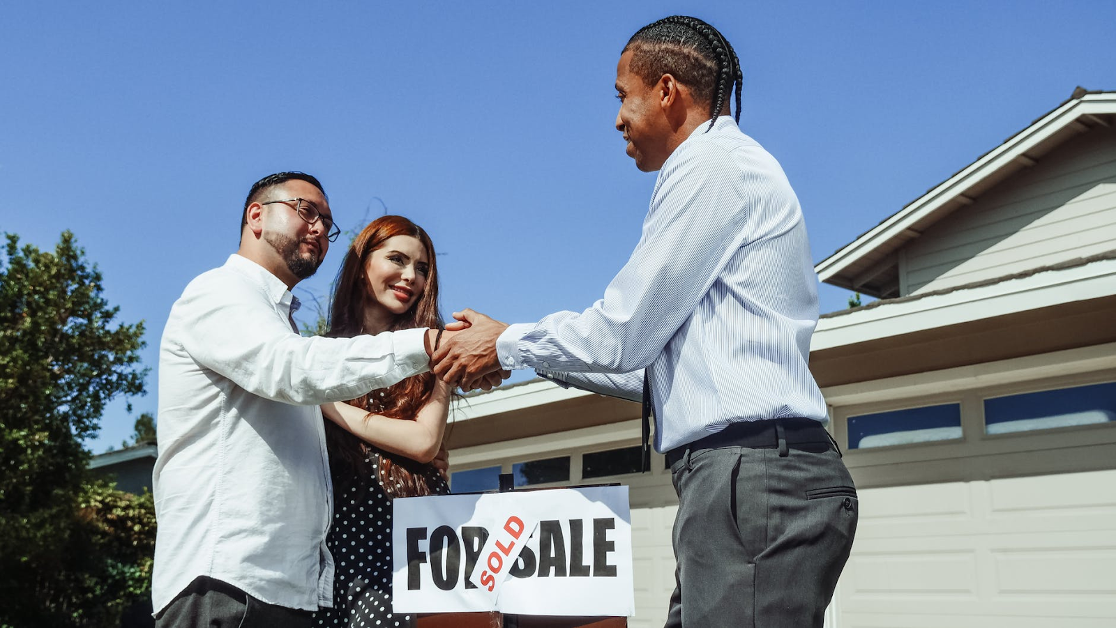 Real estate agent shaking hands with a couple after purchasing a home