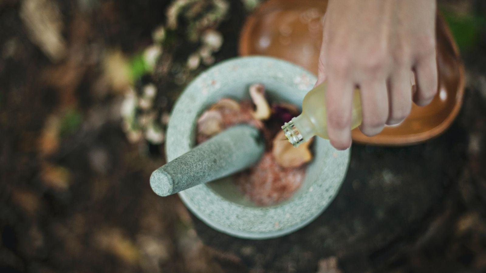 A mortar and pestle containing herbs for preparation