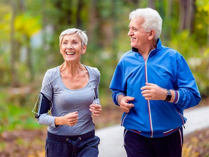 Eine ältere Frau und ein älterer Mann joggen gemeinsam durch den Wald - regelmäßiger Sport kann den Blutdruck senken.