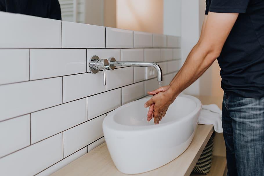 Washing hands inside the office restroom