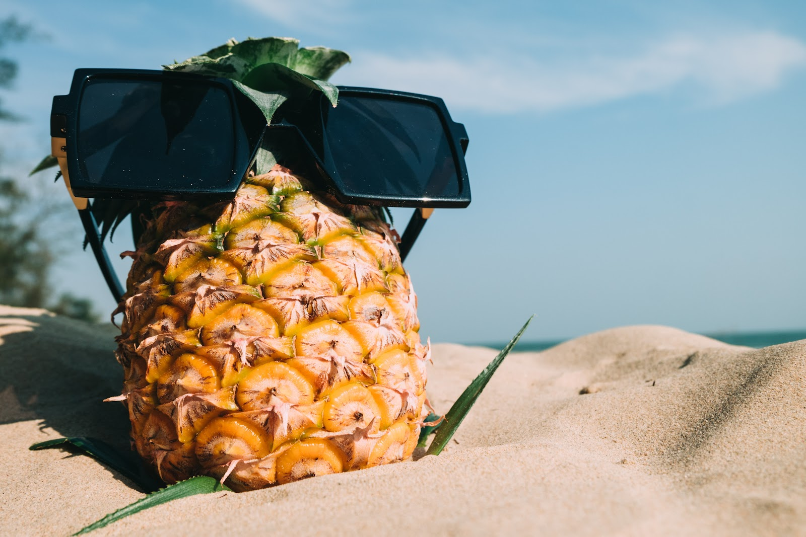 pineapple wearing sunglasses in the sand