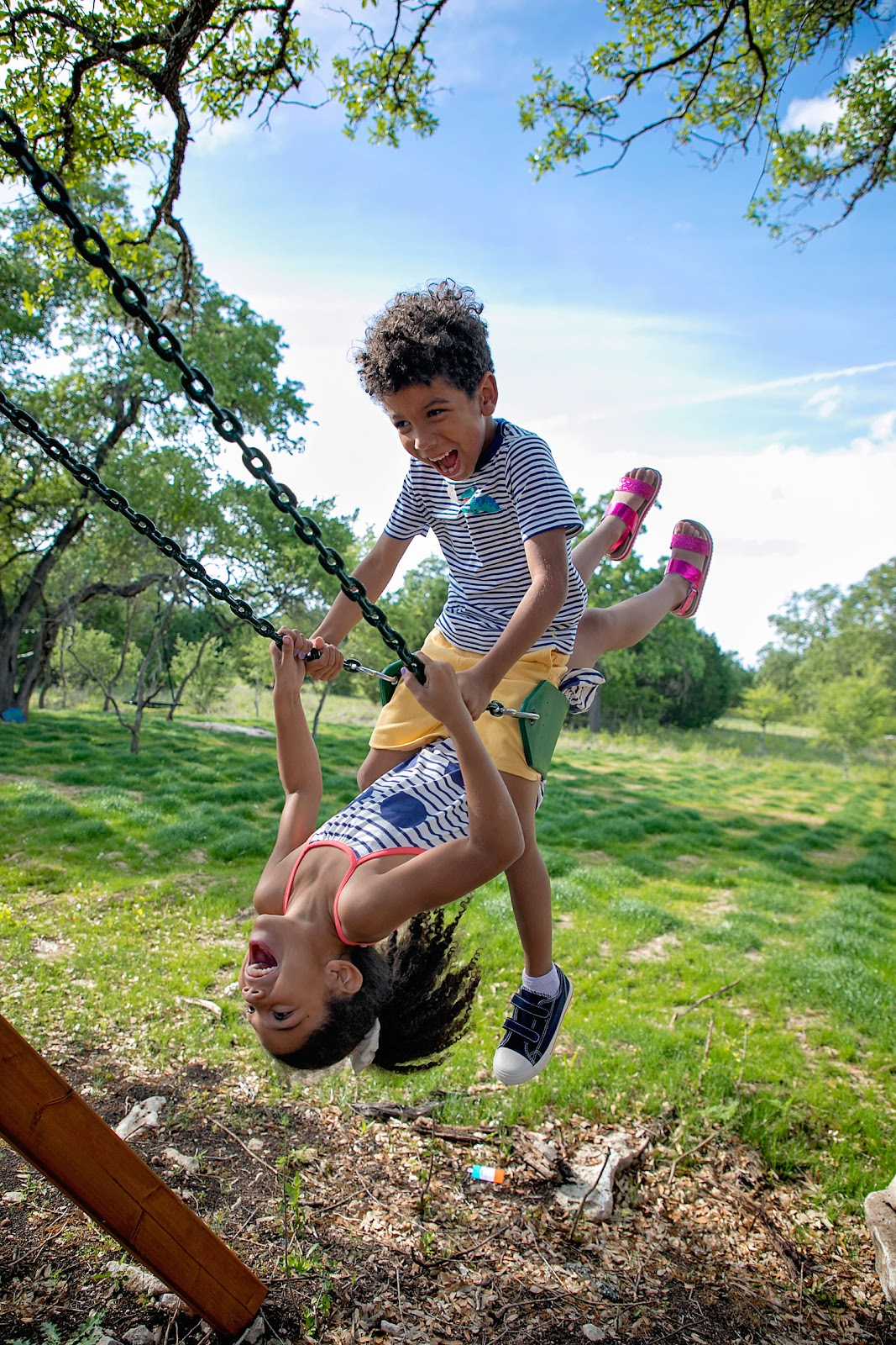 Biracial brother and sister swinging together on a swing set wearing Stitch Fix Kids.