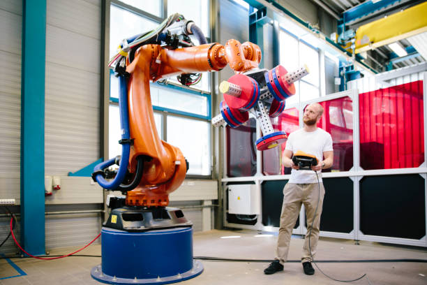 A Young engineer works at a robotic arm