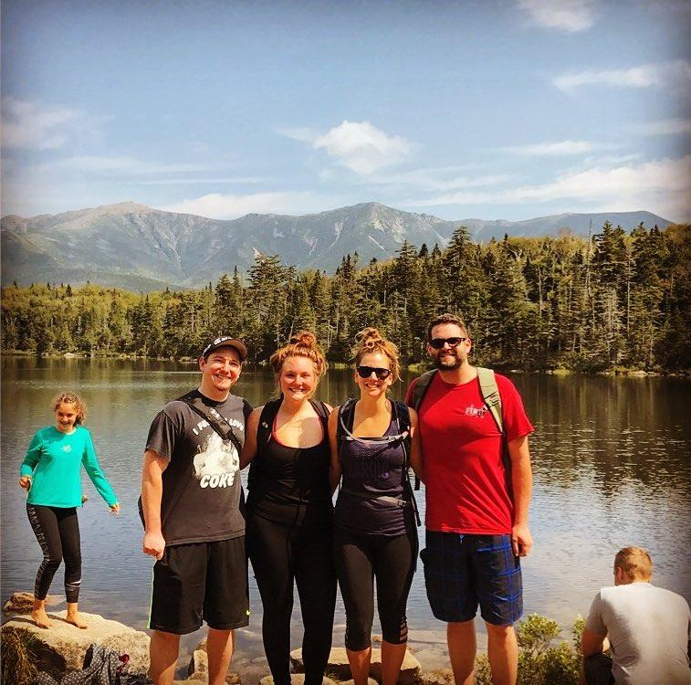 A group of people posing for a photo in front of a lake  Description automatically generated