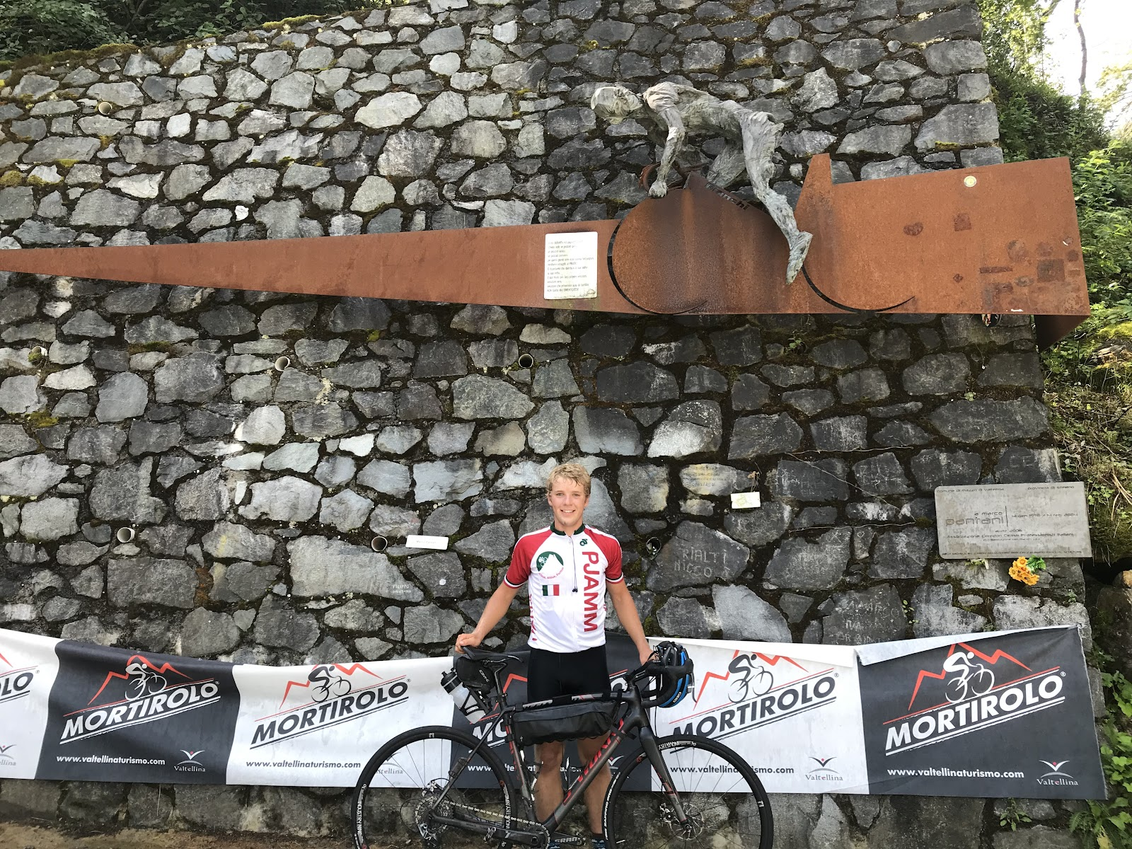 Cycling Passo del Mortirolo from Mazzo di Valtellina - PJAMM cyclists with bike at Pantani memorial
