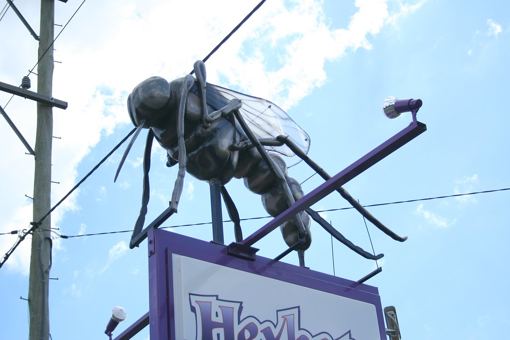 the big mosquito is a giant mosquito sculpture on top of a sign post